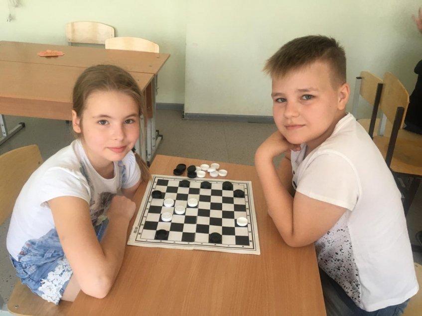Школьники с удовольствием проводят время за шашечной доской